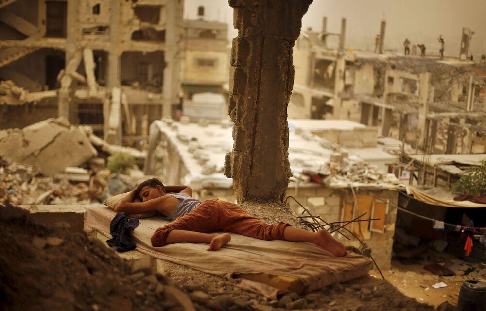 Palestyński chłopak śpi na gruzach domu jego rodziny