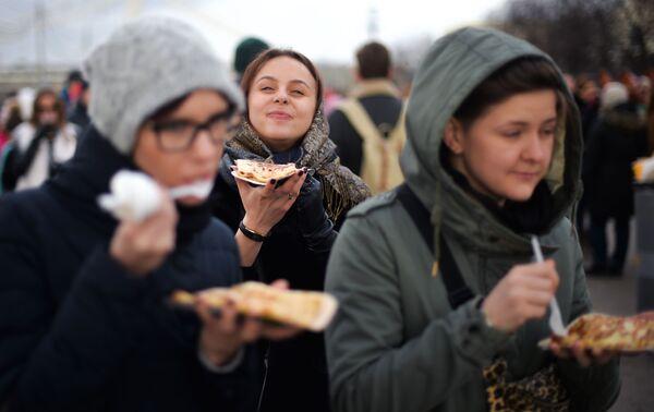 Dziewczyny jedzą bliny podczas świętowania Maslenicy w Moskwie - Sputnik Polska