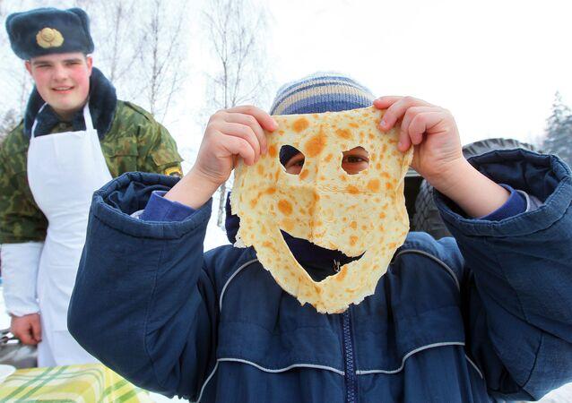 Żołnierze częstują dzieci blinami podczas obchodów Maslenicy
